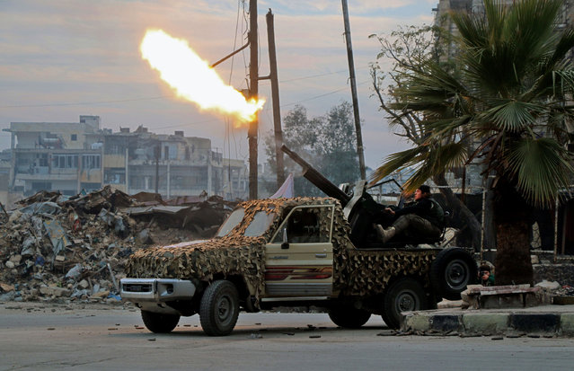 "Fighters of the Free Syrian Army fire an anti-aircraft weapon in the rebel-held Mashhad area in southeastern Aleppo, on December 12, 2016, as they battle Syrian government forces during an operation to retake the embattled city. The crucial battle for Aleppo entered its ""final phase"" after Syrian rebels retreated into a small pocket of their former bastion in the face of new army advances. The retreat leaves opposition fighters confined to just a handful of neighbourhoods in southeast Aleppo, the largest of them Sukkari and Mashhad. (Photo by AFP Photo/Stringer)"