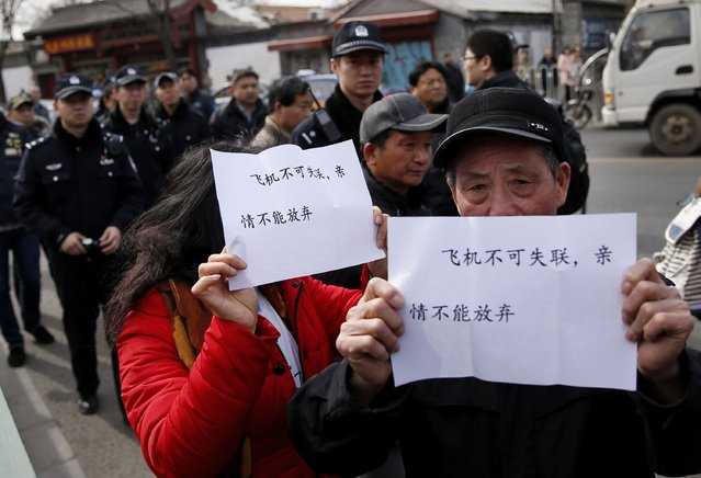 Policemen follow family members of passengers onboard the missing Malaysia Airlines flight MH370, as they hold signs outside Yonghegong Lama Temple after a gathering of family members of the missing passengers in Beijing March 8, 2015. Prime Minister Najib Razak said on Sunday Malaysia remains committed to the search for the missing MH370 jetliner a year after it vanished without trace and he is hopeful it will be found.