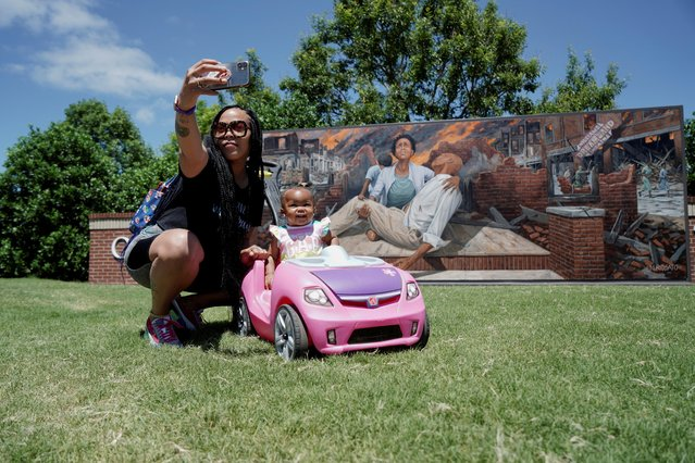 A mother and a child take a photo in front of a mural ahead of the 100th anniversary of the 1921 Tulsa Massacre in Tulsa, Oklahoma, U.S., May 29, 2021. (Photo by Lawrence Bryant/Reuters)