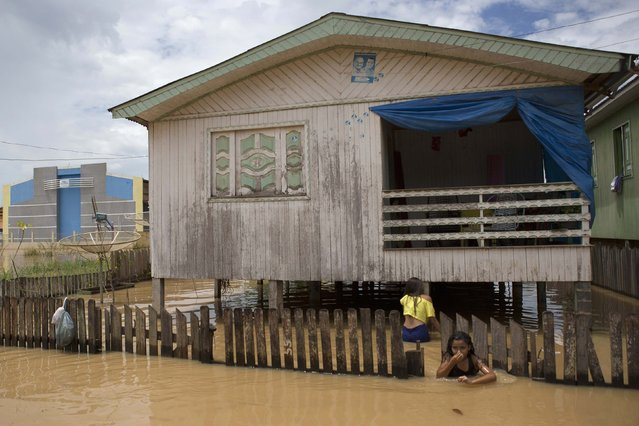 A girl leaves her home in a neighbourhood flooded by the Purus river, which continues to rise from days of heavy rainfall in the region, in Boca do Acre, Amazonas state March 14, 2015. (Photo by Bruno Kelly/Reuters)