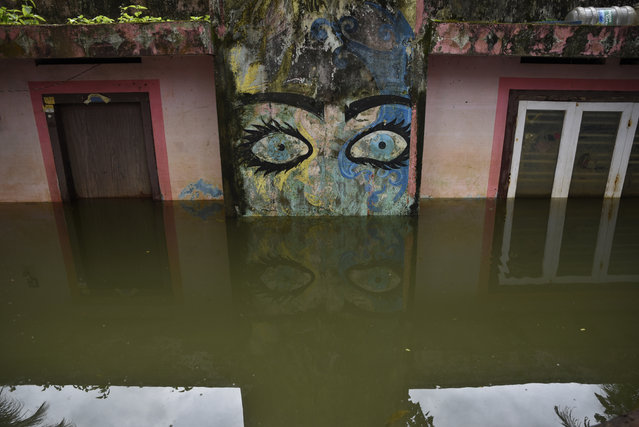 A house is seen partially submerged as flood waters recede in Kuttanad, Alappuzha in the southern state of Kerala, India, Monday, August 27, 2018. More than 300 people died and 800,000 were displaced by the worst monsoon flooding in a century in the southern Indian state of Kerala this month. (Photo by R.S. Iyer/AP Photo)