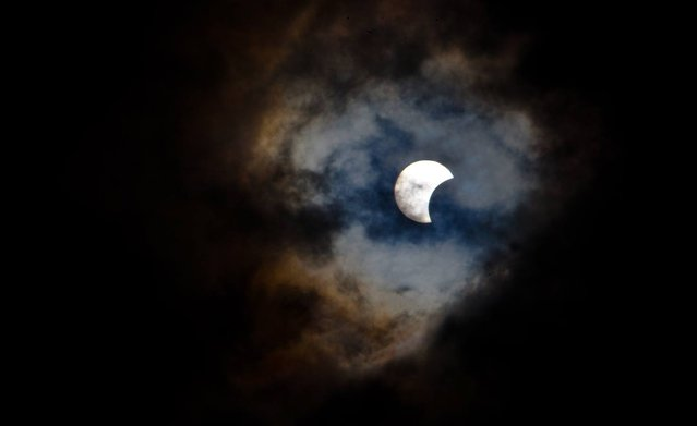 This picture taken on November 3, 2013 shows a rare hybrid solar eclipse through clouds from the Canary Island of Tenerife. A rare solar eclipse swept across parts of Africa, Europe and the United States today as the moon blocks the sun either fully or partially, depending on the location. The width of the shadow of the eclipse was 58 km and the maximum duration of totality, the maximum time that the moon covered the sun completely, was 1m 40s, on the Spanish Canary island of Tenerife. (Photo by Desiree Martin/AFP Photo)