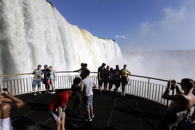 In this March 14, 2015 photo, tourists take pictures from a viewing area at Iguazu Falls in Brazil. From walkways and bridges, viewers can count 270 water falls almost 100 meters (330 feet) high. (Photo by Jorge Saenz/AP Photo)