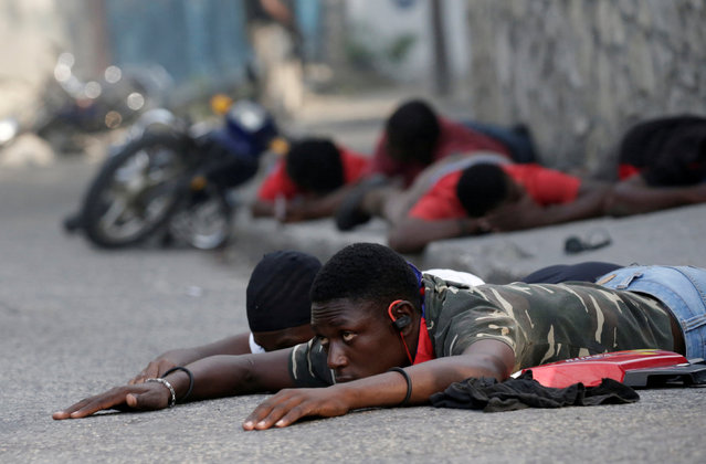 Protesters lie on the ground as they were briefly detained by the police during clashes at a demonstration called by opposition parties against the government, in the streets of Port-au-Prince, Haiti, November 23, 2018. (Photo by Andres Martinez Casares/Reuters)