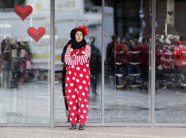 A carnival reveler stands outside a store as the traditional Rose Monday parade was canceled due to forecasted strong winds in Mainz, Germany, Monday, February 8, 2016. Duesseldorf, Mainz and Essen have joined several other German cities in calling off their main Carnival processions because of a forecast storm. Cologne plans to go ahead with its parade but has banned horses, large puppets and flags from the event for safety reasons. (Photo by Michael Probst/AP Photo)