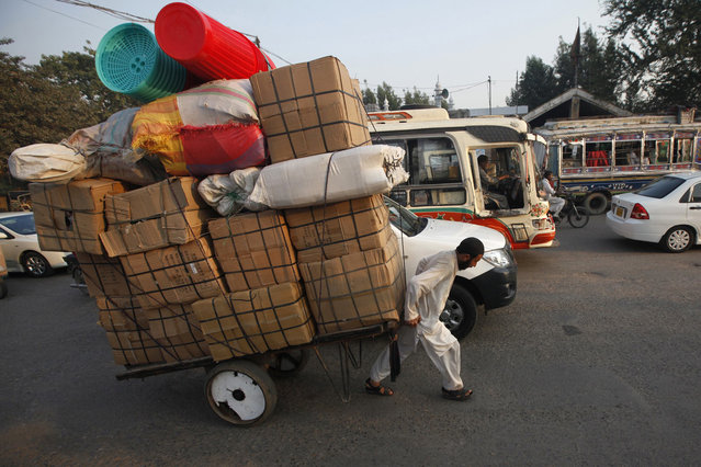 A labourer pulls a cart loaded with supplies while heading to a nearby market in Karachi November 28, 2013. (Photo by Athar Hussain/Reuters)