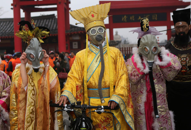 "Anti-pollution protesters wearing traditional costumes and contemporary gas masks ride bicycles in the Qingming Grand river park in Kaifeng, Henan Province, China on January 1, 2017. The Beijing Municipal Environmental Protection Bureau extended an ""orange alert"" for heavy air pollution for three more days. (Photo by SIPA Asia/Rex Features/Shutterstock)"