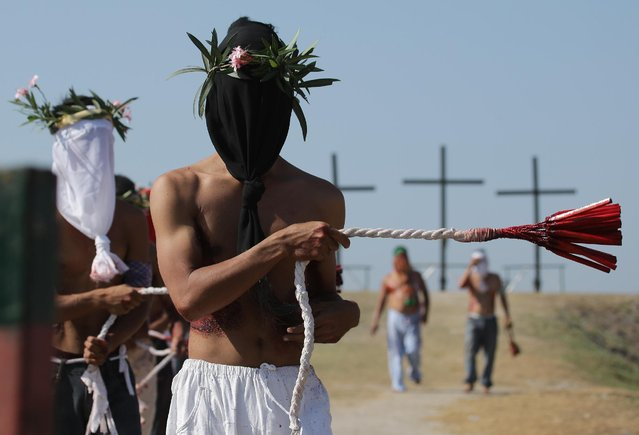 Hooded Filipino penitents flagellate during Good Friday rituals to atone for sins on Friday, April 3, 2015 in Pampanga province, northern Philippines. The ritual is frowned upon by church leaders in this predominantly Roman Catholic country. (Photo by Aaron Favila/AP Photo)