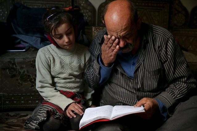 Shahrour, 54, looks at his daughter Hadeel's notebook inside their home in the besieged town of Arbeen, in Damascus suburbs, Syria February 6, 2016. (Photo by Bassam Khabieh/Reuters)