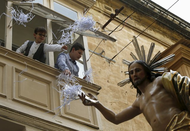 Children throw confetti from a balcony over a statue of the Risen Christ during an Easter Sunday procession in Cospicua, outside Valletta April 5, 2015. (Photo by Darrin Zammit Lupi/Reuters)