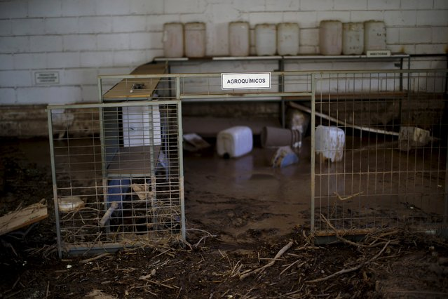 "A view of a muddy room in a flooded warehouse at an agricultural company in Los Loros town April 7, 2015. The sign reads ""Agrochemicals"". (Photo by Ivan Alvarado/Reuters)"