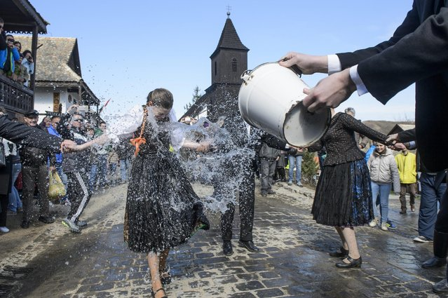 Dressed in folk costumes, young men pour water from their buckets on young women in Holloko, a mountain village enlisted on the World Heritage List of Unesco, some 80 kms northeast of Budapest, Hungary, Monday, April 6, 2015. (Photo by Peter Komka/AP Photo/MTI)