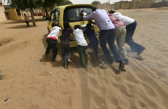 People push a car stuck in the sand during registeration for a Darfur referendum, on whether to remain as five states or merge into one, at Al Fashir in North Darfur February 17, 2016. (Photo by Mohamed Nureldin Abdallah/Reuters)