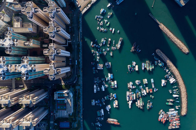 This aerial photo taken on October 29, 2018 shows boats moored at a typhoon shelter next to residential buildings in Hong Kong. (Photo by Dale De La Rey/AFP Photo)
