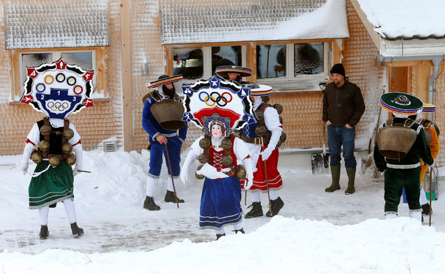 """A man watches men dressed as """"Chlaeuse"""", figures that scare away evil spirits, carry round bells and cowbells as they perform during the traditional """"Sylvesterchlausen"""" near the northeastern village of Urnaesch, Switzerland January 13, 2017. (Photo by Arnd Wiegmann/Reuters)"""