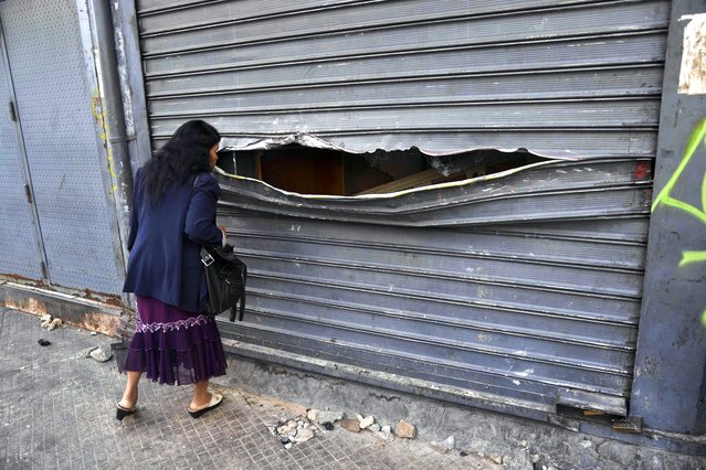 A woman peeps through the vandalised curtain of a store that was looted during protests the night before in Caracas, Venezuela on January 24, 2019. UN chief Antonio Guterres on Thursday appealed for dialogue to stop Venezuela's political crisis spiralling out of control, after opposition leader Juan Guaido declared himself interim president. (Photo by Yuri Cortéz/AFP Photo)