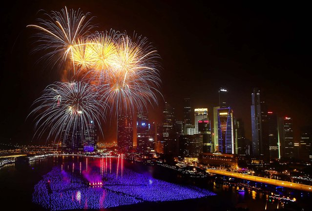 Fireworks explode over the financial district in Singapore. (Photo by Wong Maye-E/Associated Press)