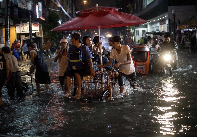Rickshaw driver carrying passengers manoeuvers on a flooded street due to a heavy downpour brought about by tropical storm Yagi as it exits the Philippine's area of responsibility, in Manila on August 11, 2018, with commuters stranded as they wait for their ride back home. (Photo by Noel Celis/AFP Photo)
