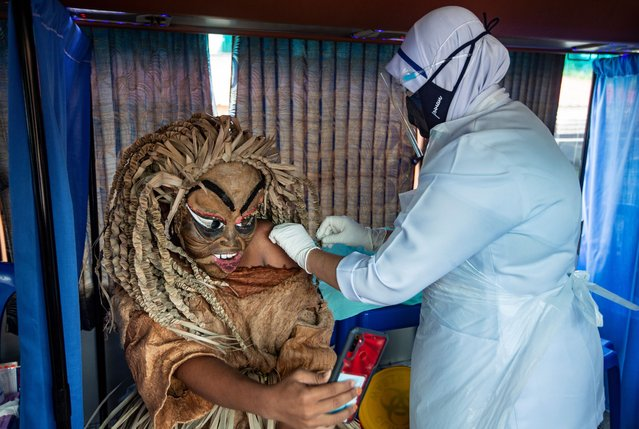 An indigenous man of Mahmeri tribe wearing a costume of Puteri Gunung Ledang character receives a dose of the vaccine against Covid-19 in Banting, near Kuala Lumpur, Malaysia,15 August 2021. Malaysia recorded another 20,670 new Covid-19 cases on 14 August, bringing the cumulative total to 1,384,353 cases. (Photo by Ahmad Yusni/EPA/EFE)