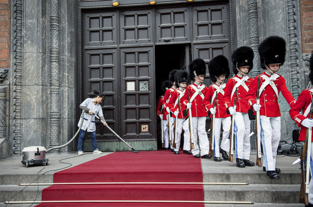 A cleaning lady vacuums the red carpet as preparations are under way before Queen Margrethe is received at the City Hall, hosting a lunch reception on the occasion of her 75th birthday in Copenhagen, Denmark, April 16, 2015. (Photo by Mathias Bojesen/EPA)