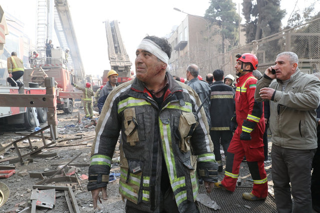 A wounded firefighter stands at the site of a collapsed high-rise building in Tehran, Iran January 19, 2017. At least 20 firefighters have been killed after responding to a huge fire in a commercial high rise building in Tehran, which caused the structure to collapse. Iranian state media said it is believed people are still trapped beneath the rubble and that rescue efforts could go on for a further two days. (Photo by Mahmoud Hosseini/Reuters/Tasnim News Agency)