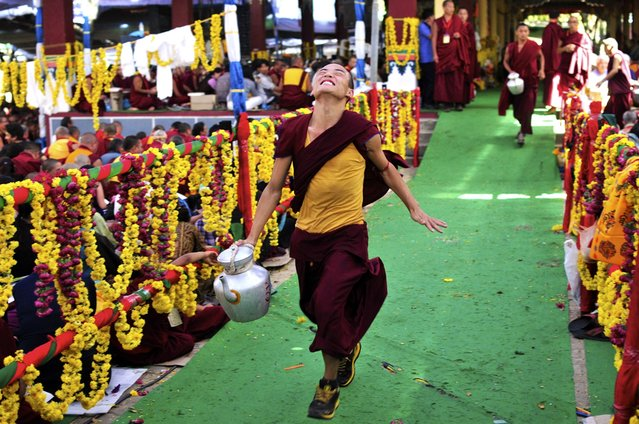 A Tibetan Buddhist monk runs in joy after serving butter tea to high priests attending the Jangchup Lamrim teachings at the Sera Monastery in Bylakuppe, about 135 miles west of Bangalore, India, Wednesday, January 1, 2014. The ten-day teachings began December 25, 2013. (Photo by Abhishek N. Chinnappa/AP Photo)
