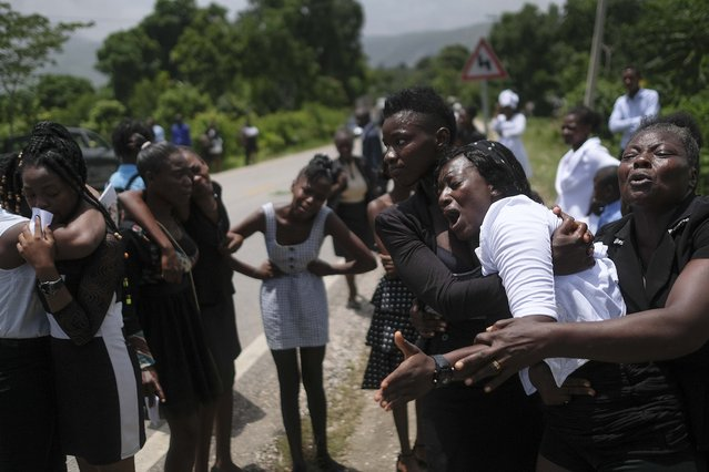 Relatives mourn during the funeral of Baptist church minister Andre Tessono, who was killed during 7.2 magnitude earthquake hit the area 8 days ago, in the Picot neighborhood in Les Cayes, Haiti, Sunday, August 22, 2021. (Photo by Matias Delacroix/AP Photo)