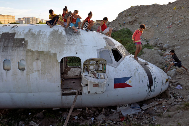 Children play on top of an old plane's fuselage at a dump site in Paranaque city, Metro Manila, Philippines January 21, 2017. (Photo by Ezra Acayan/Reuters)