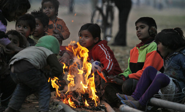 Children sit around a small bonfire on a cold and foggy morning on January 8, 2014 in New Delhi, India. Delhi saw the minimum temperature registering a dip from the 6.1 degrees Celsius recorded yesterday to settle at 4.4 degrees, which was three degrees below normal.Large swathes of north India bore the brunt of cold wave and icy winds as temperature in several parts of the region breached the sub zero level, disrupting rail, and road and air traffic. (Photo by Raj k Raj/Hindustan Times via Getty Images)