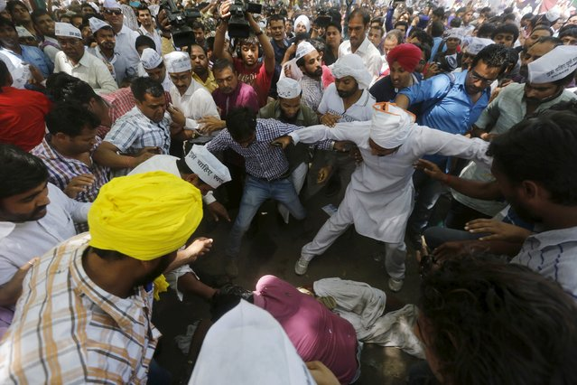 Protesters gather around a farmer who hung himself from a tree during a rally organized by AAP, in New Delhi April 22, 2015. (Photo by Adnan Abidi/Reuters)