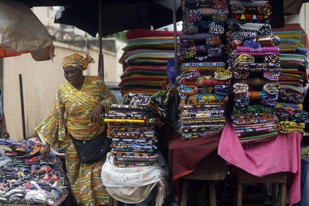 A woman sells fabrics at Kaporo market in Conakry, Guinea Monday, September 13, 2021. (Photo by Sunday Alamba/AP Photo)