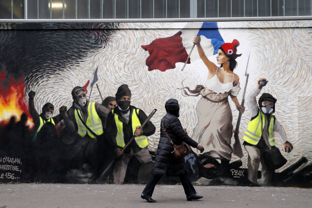 """A woman passes by a mural by street artist PBOY depicting Yellow Vest (gilets jaunes) protestors inspired by a painting by Eugene Delacroix, """"La Liberte guidant le Peuple"""" (Liberty Leading the People), in Paris, Thursday, January 10, 2019. French President Emmanuel Macron is facing a mountain of challenges in the new year starting with yellow vest protesters who are back in the streets to show their anger against high taxes and his pro-business policies that they see as favoring the wealthy rather than the working class. (Photo by Christophe Ena/AP Photo)"""
