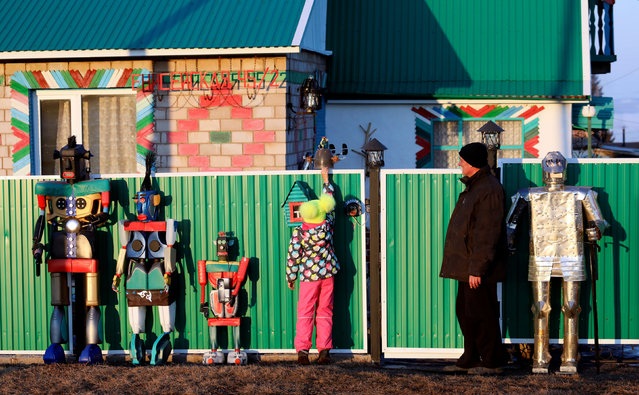Local resident Gennady Chereshkevich speaks with his granddaughter Vlada while showing fancy sculptures, which he made of plastic, metal canisters and other materials for the decoration of his house, in the settlement of Novosyolovo south of Krasnoyarsk, Russia March 7, 2019. (Photo by Ilya Naymushin/Reuters)