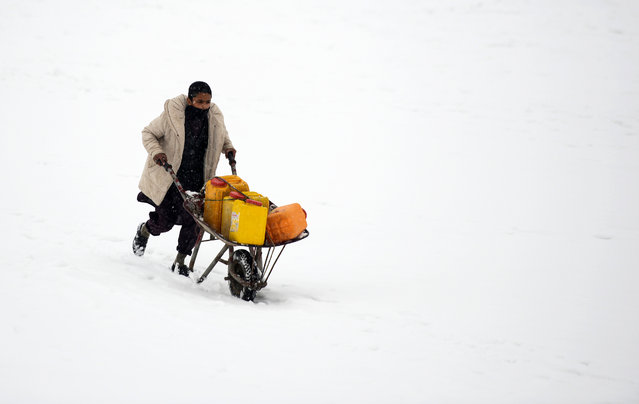 An Afghan man pushes a wheelbarrow as he carries water cans during the snowfall in Kabul on January 10, 2019. (Photo by Wakil Kohsar/AFP Photo)