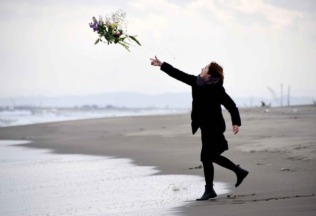A woman throws flowers into the sea to pray for victims of the 2011 earthquake and tsunami in Sendai, northern Japan on March 11, 2016. Japan marked the fifth anniversary of the March 11 quake and tsunami that claimed some 18,500 lives, flattened coastal communities and set off the worst atomic crisis in a generation. (Photo by Toru Yamanaka/AFP Photo)