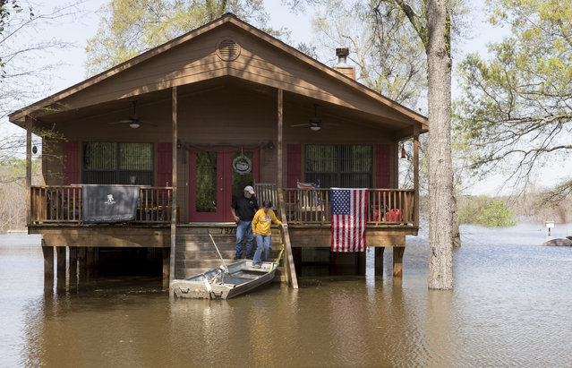 Residents make there way to a boat as water from Caddo Lake surrounds the raised house in Mooringsport, La., Sunday, March 13, 2016. President Barack Obama has signed an order declaring Louisiana's widespread flooding from heavy rains a major disaster. (Photo by Lee Celano/The Shreveport Times via AP Photo)