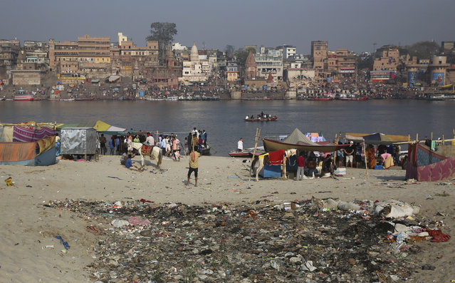 In this March 22, 2019, photo, trash is strewn on the banks of river Ganges, in Varanasi, India. Modi promised to clean up the Ganges, but gray water continues flowing not far from the banks where crowds of devotees and tourists converge for a nightly prayer. In the Indian city considered the center of the Hindu universe, Prime Minister Narendra Modi has commissioned a grand promenade connecting the sacred Ganges river with a centuries-old temple dedicated to Lord Shiva, the god of destruction. (Photo by Altaf Qadri/AP Photo)