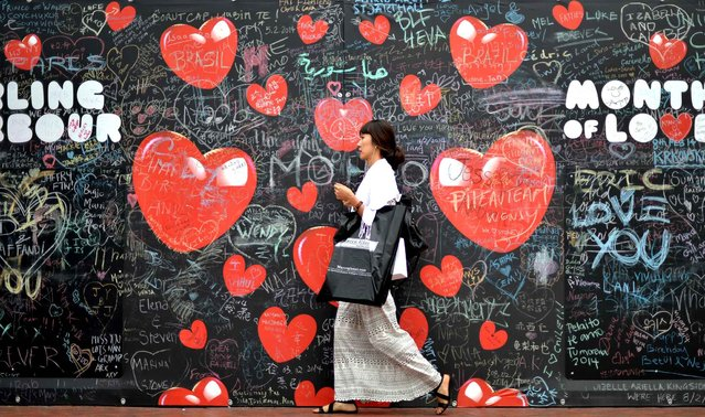 A woman walks past a partition wall full of Valentines Day messages at the Darling Harbour in Sydney on February 13, 2014. Red roses and chocolates are the most popular gifts during Valentines Day. (Photo by Saeed Khan/AFP Photo)