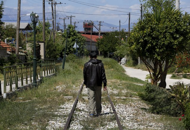 An Afghan immigrant walks on unused rail tracks by the ferry terminal in the western Greek town of Patras May 4, 2015. (Photo by Yannis Behrakis/Reuters)