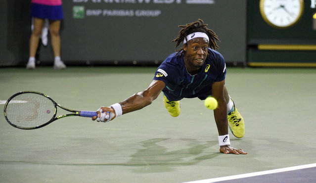 Gael Monfils, of France, dives as he returns a shot to Milos Raonic, of Canada, at the BNP Paribas Open tennis tournament, Thursday, March 17, 2016, in Indian Wells, Calif. Raonic won 7-5, 6-3. (Photo by Mark J. Terrill/AP Photo)