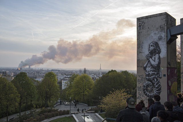 People watch Notre Dame cathedral burning in Paris, Monday, April 15, 2019. Massive plumes of yellow brown smoke is filling the air above Notre Dame Cathedral and ash is falling on tourists and others around the island that marks the center of Paris. (Photo by Rafael Yaghobzadeh/AP Photo)