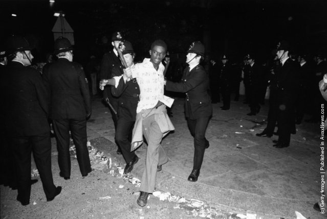 Police arresting a young black man during riots at the Notting Hill Carnival in west London, 1977