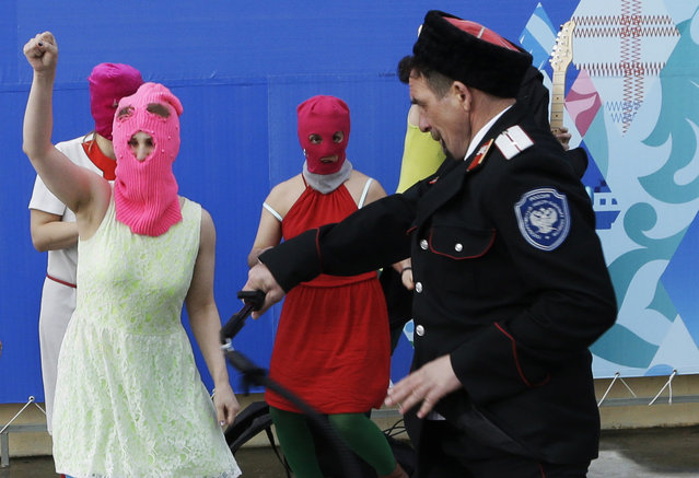 Members of the punk group p*ssy Riot, including Nadezhda Tolokonnikova in the blue balaclava and Maria Alekhina in the pink balaclava, are attacked by Cossack militia in Sochi, Russia, on Wednesday, February 19, 2014. (Photo by Morry Gash/AP Photo)