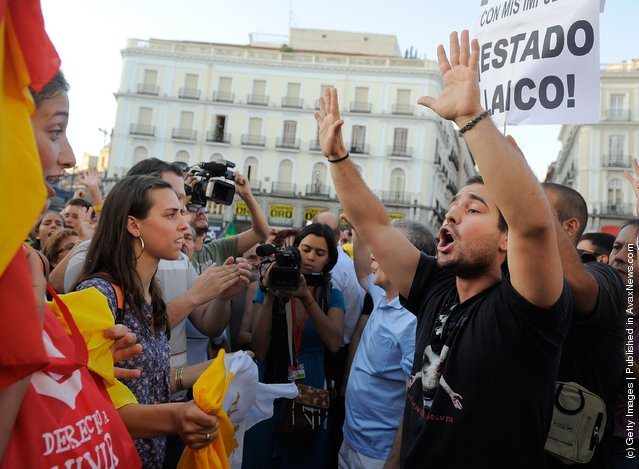 Pro (L) and anti World Youth Day supporters face off at Puerta del Sol square during a march against the papal events taking place