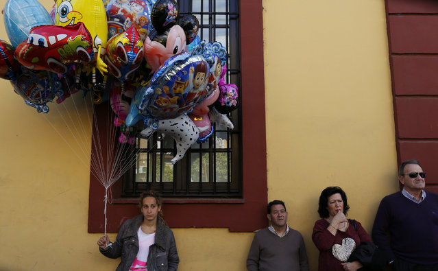 A ballon seller and bystanders watch the procession of San Bernardo brotherhood during Holy Week in the Andalusian capital of Seville, southern Spain March 23, 2016. (Photo by Marcelo del Pozo/Reuters)