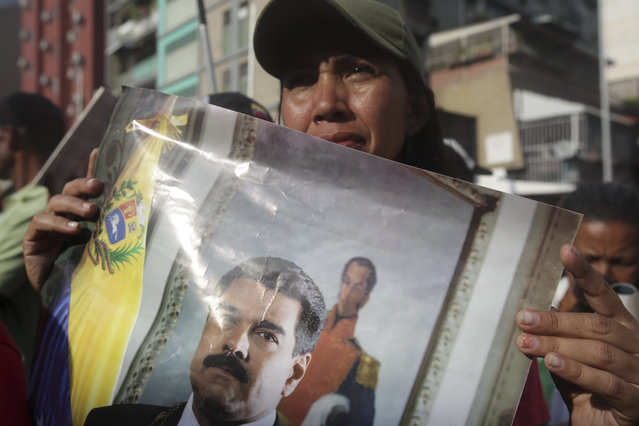 A supporter of Venezuela's President Nicolas Maduro holds a poster of him outside Miraflores presidential palace during an attempted military uprising in Caracas, Venezuela, Tuesday, April 30, 2019. Venezuelan opposition leader Juan Guaidó and jailed opposition leader Leopoldo Lopez took to the streets with a small contingent of armed troops early Tuesday in a call for the military to rise up and oust Maduro. (Photo by Boris Vergara/AP Photo)