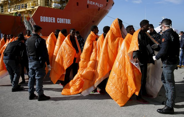 Migrants are inspected by policemen as they disembark  from the Norwegian vessel Siem Pilot at Pozzallo's harbour, Italy, March 29, 2016. (Photo by Antonio Parrinello/Reuters)