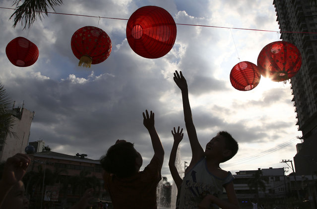 Filipino boys play with red lanterns that are displayed at a park in Manila, Philippines on Friday, March 1, 2019 (Photo by Aaron Favila/AP Photo)