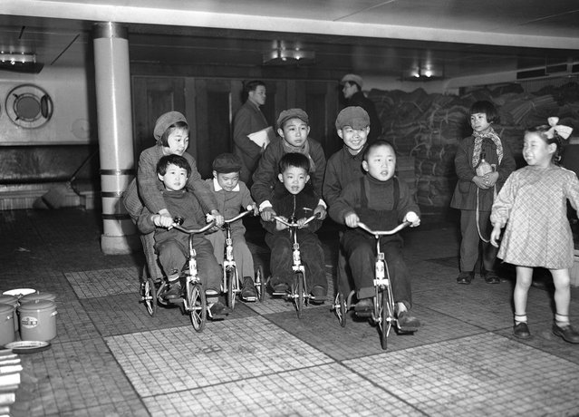 Children of repatriated families scoot around the deck of the Koan Maru as their parents prepare to disembark at Maizuru Bay, Japan, on March 24, 1953. The first group of repatriates to be returned from Communist China where they had been stranded since the end of World War II completed the formalities through the processing center at Maizuru and were released to go home. (Photo by Y. Jackson Ishizaki/AP Photo via The Atlantic)