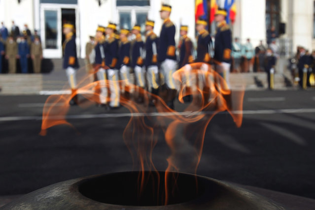 Romanian soldiers are seen through the flame of unknown soldier while standing in attention during celebrations marking the NATO Day in Bucharest 03 April 2016. Romania became a full member of NATO on 02 April 2004. (Photo by Bogdan Cristel/EPA)